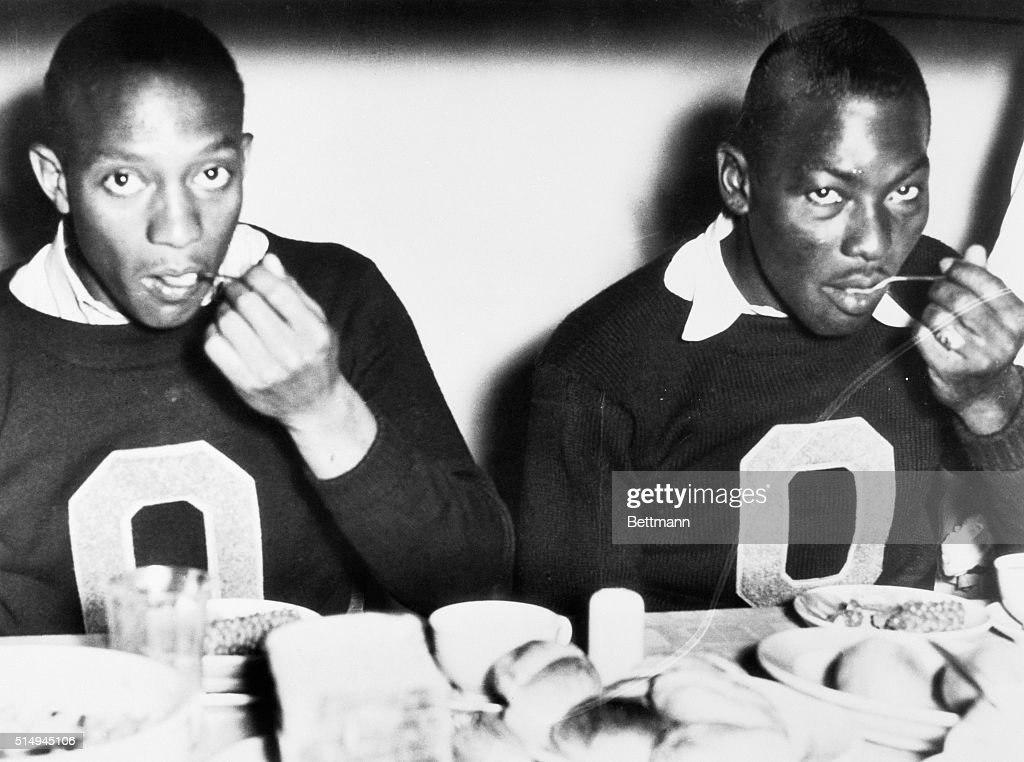 American track and field competitors Jesse Owens and Dave Albritton eat dinner in the Olympic Village during the 1936 Summer Olympics in Berlin