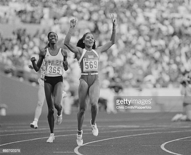American track athlete Florence Griffith Joyner raises her arms in the air in celebration after crossing the finish line in first place to win the...