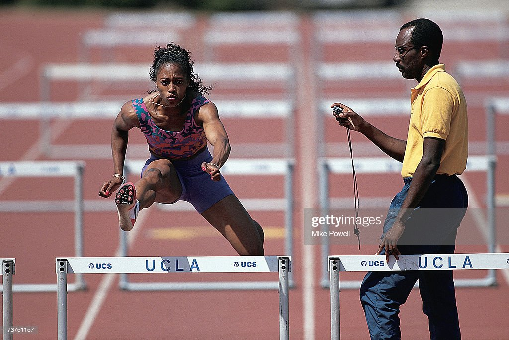 American track coach Bobby Kersee times runner Gail Devers as she jumps a hurdle in 1988 at Drake Stadium on the campus of UCLA in Westwood California