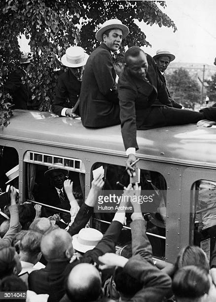 American trackandfield athlete Jesse Owens signs autographs for German fans from atop the US Olympic Team's bus during the opening ceremonies of the...