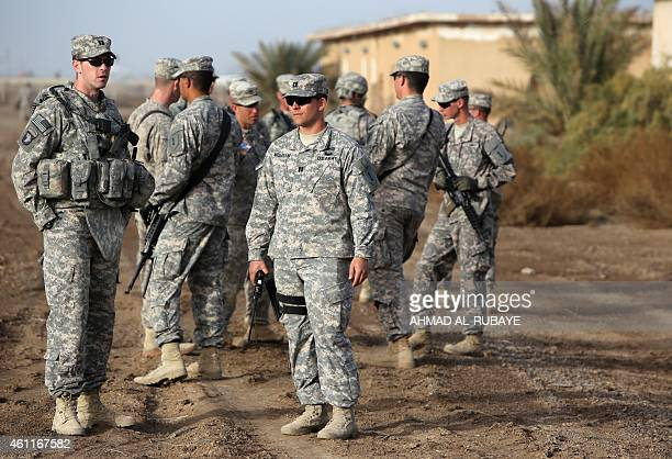 American trainers take a break as they train Iraqi soldier on approaching and clearing buildings at the Taji base complex which hosts Iraqi and US...