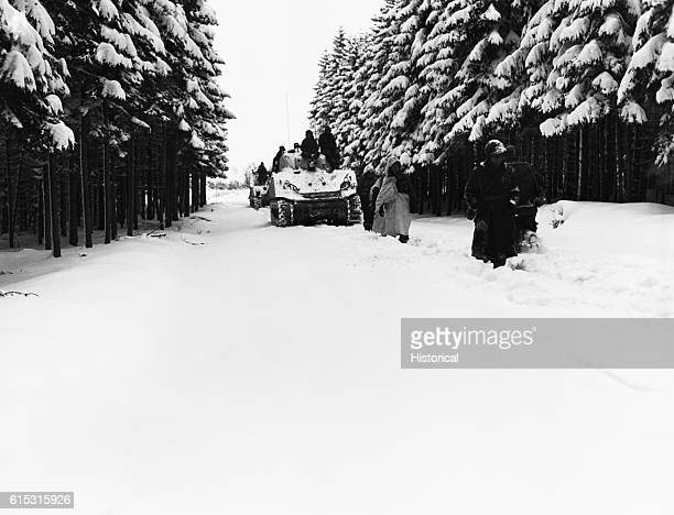 American troops and tanks travel through deep snow to reach Heersbach[] during the Battle of the Bulge Belgium 1945 | Location near Heersbach Belgium