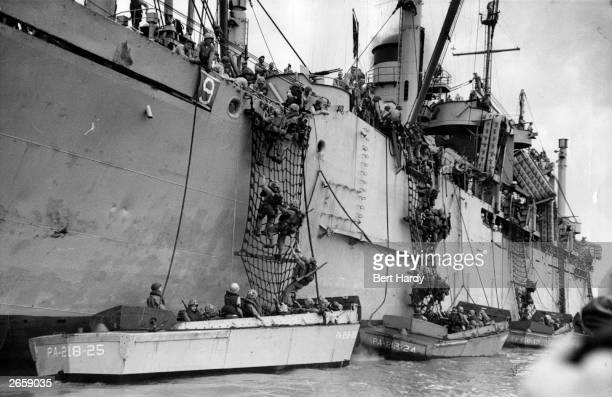 American troops climbing down guide nets into assault craft in preparation for the first great counterstrike of the Korean campaign Original...