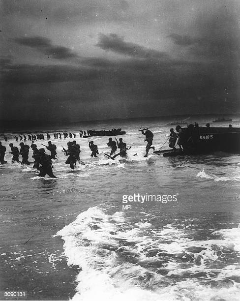 American troops jump from a landing craft and wade through water on to a beach under a dark cloudstreaked sky