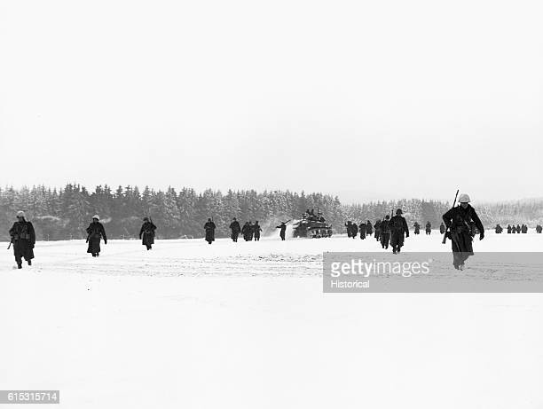 American troops of the 84th Infantry Division advance through a snowfield in France towards La Roche Belgium during the Battle of the Bulge January...