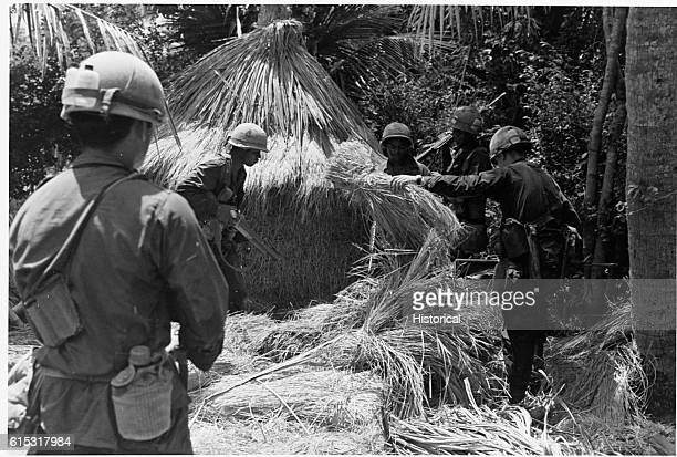 American troops search for Vietcong insurgents in a village South Vietnam 1966 | Location unidentified village in South Vietnam