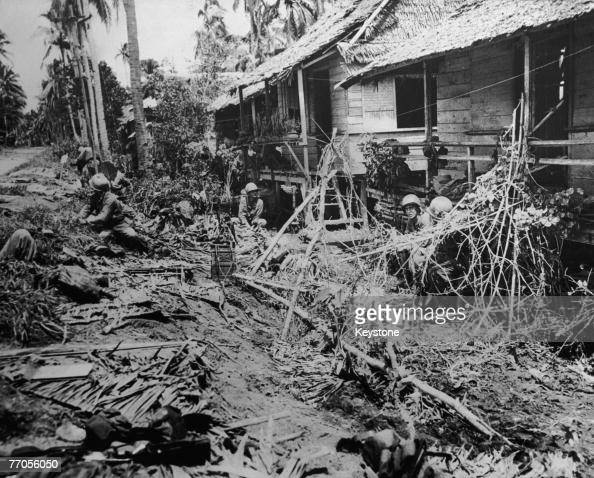 American troops take cover during streetfighting in the bombdamaged village of Pawing in Leyte province in the Philippines during the Battle of Leyte...