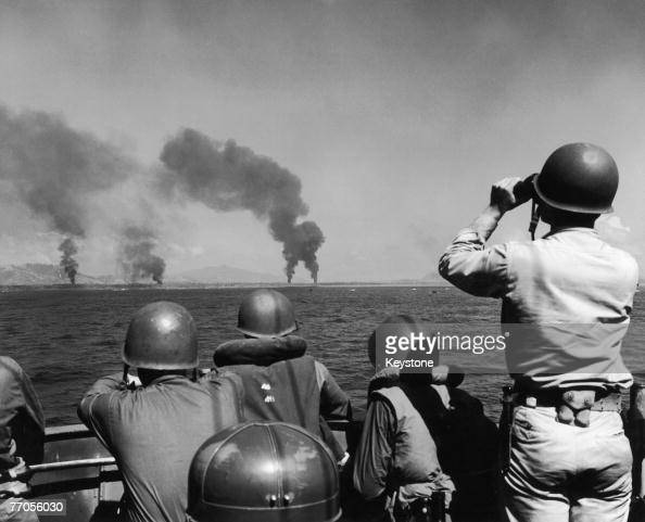 American troops watch columns of smoke rising from the coast of Leyte province in the Philippines after preliminary bombardments leading to the...