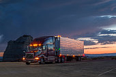 American Truck diagonal view in sunset with dark cloud