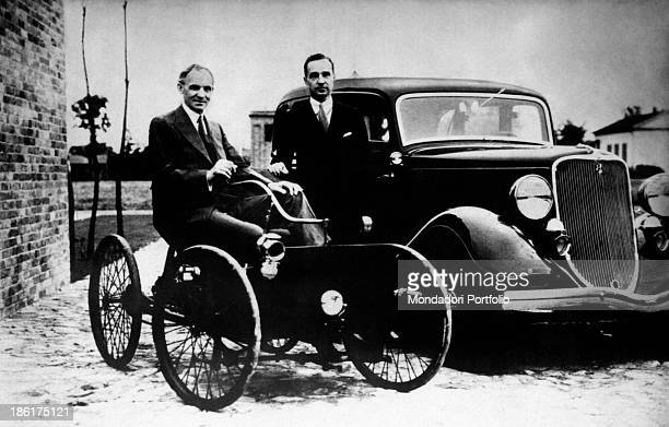 American tycoon Henry Ford and his son Edsel Ford posing with two cars manufactured by their carmaking company 1930s