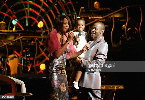 Whitney Houston with her daughter Bobbi Kristina Brown and husband Bobbi Brown onstage during a concert on July 16 1999 in New York City
