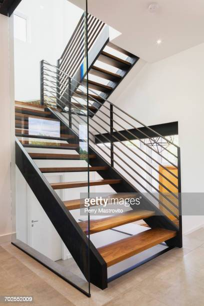 American walnut wood and black powder coated cold rolled steel stairs inside a modern cube style home, Quebec, Canada