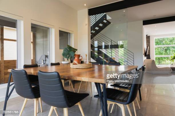 American walnut wood dining table and black leather sitting chairs with ash wood legs in the dining room inside a modern cube style home, Quebec, Canada