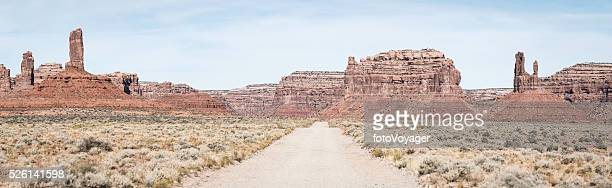 American West desert road through Monument Valley mesas pinnacles panorama