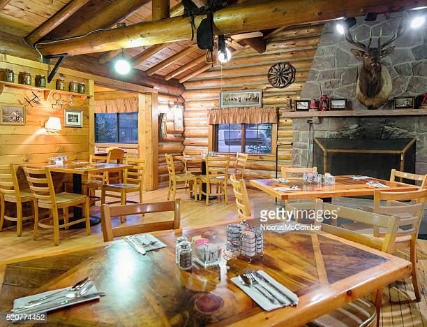 American Western log cabin restaurant dining room with fireplace
