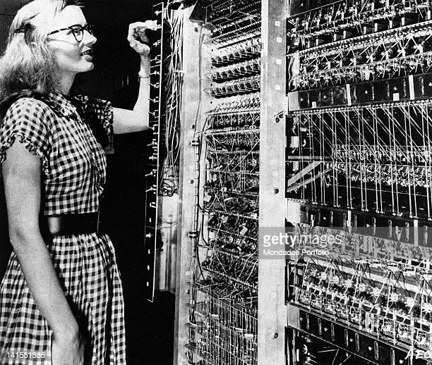 American woman standing next to a Maniac calculator USA 1954