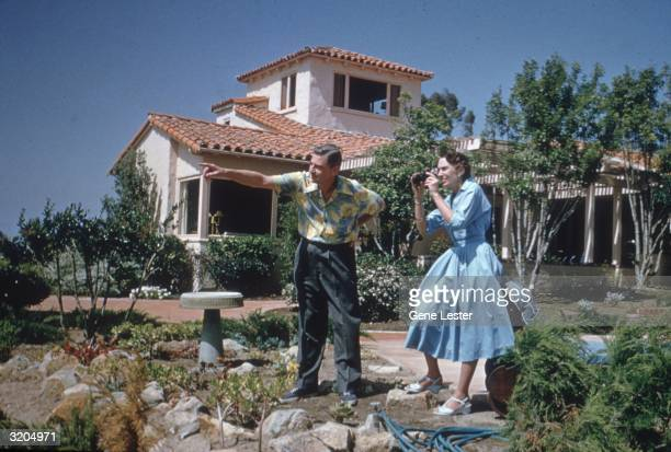 American writer and illustrator Dr Seuss points towards something in the distance while his wife Helen prepares to take a picture outside their home...