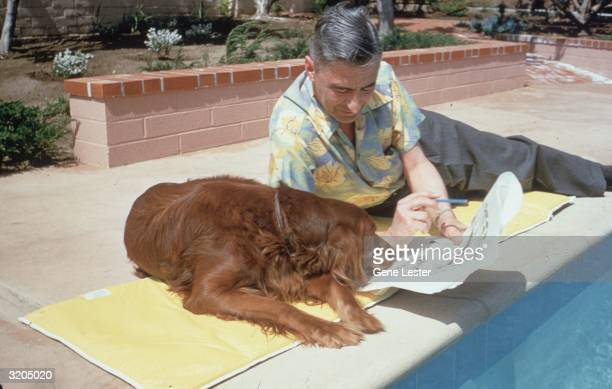American writer and illustrator Dr Seuss reclines with his Irish setter Cluny and some proofs of his work by the edge of a swimming pool at home in...