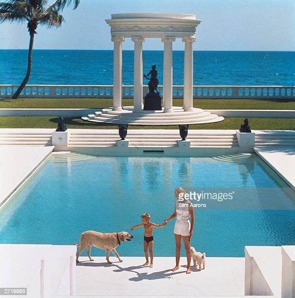 American writer CZ Guest and her son Alexander Michael Douglas Dudley Guest in front of their Grecian temple pool on the oceanfront estate Villa...