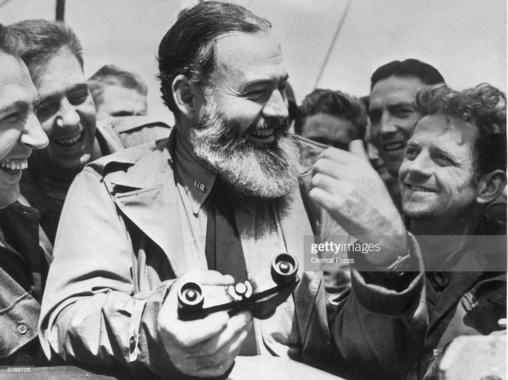 American writer <a gi-track='captionPersonalityLinkClicked' href=/galleries/search?phrase=Ernest+Hemingway&family=editorial&specificpeople=93360 ng-click='$event.stopPropagation()'>Ernest Hemingway</a> (1899 - 1961) travelling with US soldiers, in his capacity as war correspondent, on their way to Normandy for the D-Day landings.