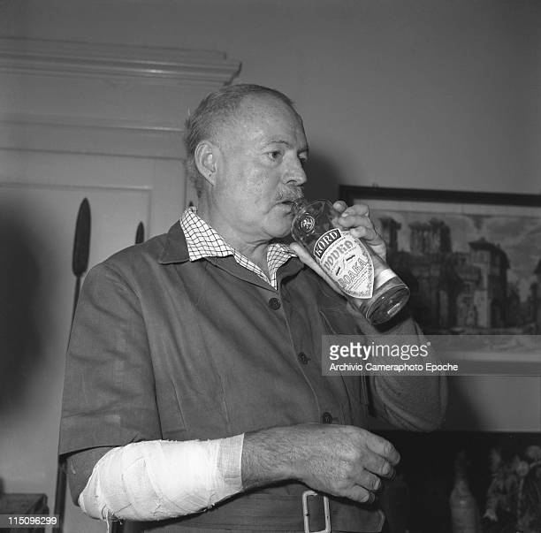 American writer Ernest Hemingway wearing a short sleeves shirt over a plaid shirt his hurted arm bendaged drinking vodka from the bottle Venice 1954