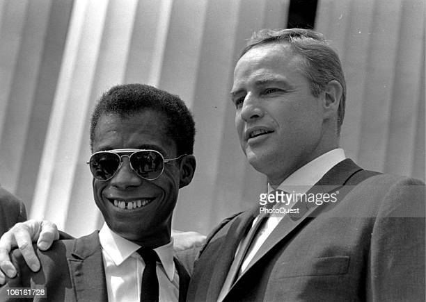 American writer James Baldwin smiles as he poses with actor Marlon Brando outside the Lincoln Memorial during the March on Washington for Jobs and...