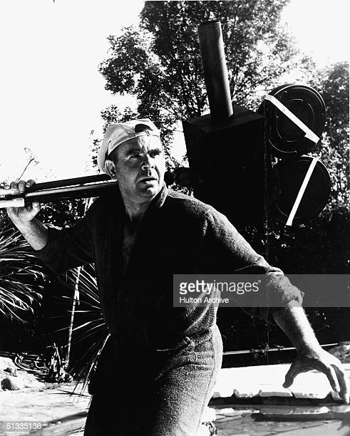 American writer producer director editor and actor Russ Meyer carries an obviously fake prop movie camera and wears a bathrobe and backwards hat...