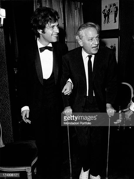 Americanborn French singer Joe Dassin helping his father American director Jules Dassin walking on crutches Paris 1970