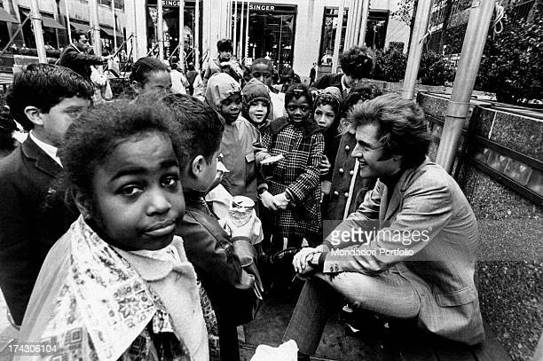 Americanborn French singer Joe Dassin smiling to a group of children Paris 1970