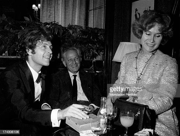 Americanborn French singer Joe Dassin smoking a cigar at the table of a bar Beside him his father American director Jules Dassin and his mother...