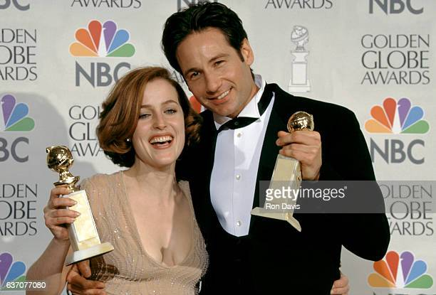 AmericanBritish actress Gillian Anderson and American actor David Duchovny hold their Golden Globes in the press room during the 54th Annual Golden...