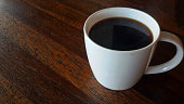 americano coffee in white mug on wooden table