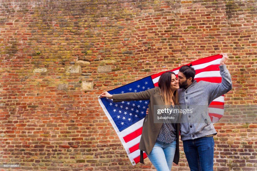 Americans holding Ameican flag in front of brick wall : Stock Photo