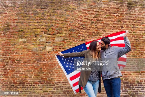 Americans holding Ameican flag in front of brick wall : Foto stock