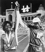 America's Al Joyner who won Gold in the Triple Jump 8/4 raises hand of his sister Jackie who won a Silver in the Women's Heptathalon