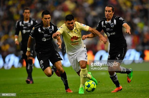 America's forward Silvio Romero vies for the ball with Monterrey's defender Efrain Juarez and midfielder Jesus Molina during their Mexican Clausura...