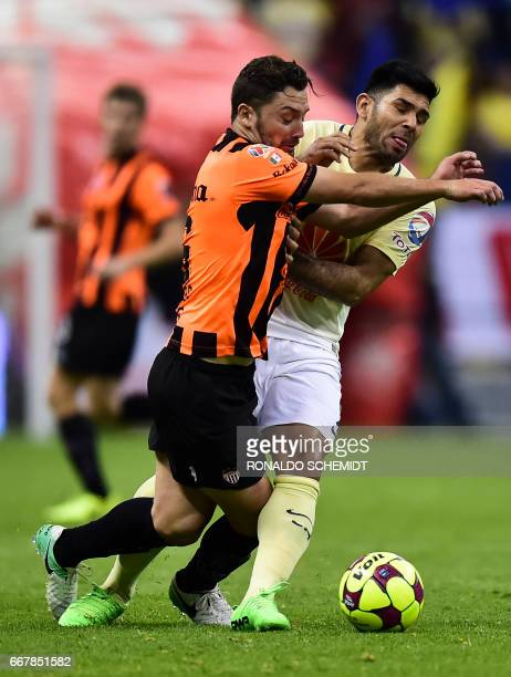 America´s Silvio Romero vies for the ball with Necaxa´s Manuel Iturra during their Mexican Clausura 2017 tournament football match at the Azteca...