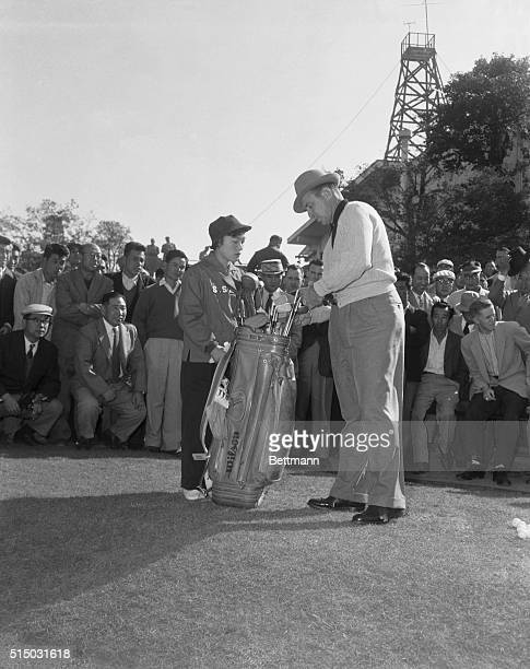 America's Slammin' Sam Snead selects a club from bag held by his Japanese girl caddy during first day of play in the Canada Cup matches at Japan's...