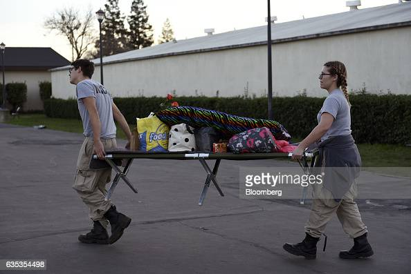 Americorps volunteers carry a cot with donated items at the Silver Dollar Fairgrounds evacuation center in Chico California US on Tuesday Feb 14 2017...