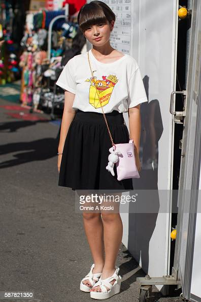 Ami Ito is seen on Meiji St wearing a white WeGo graphic tee a black skirt by Seshirumakuri white wedge sandals by Spins and a small pink chain bag...