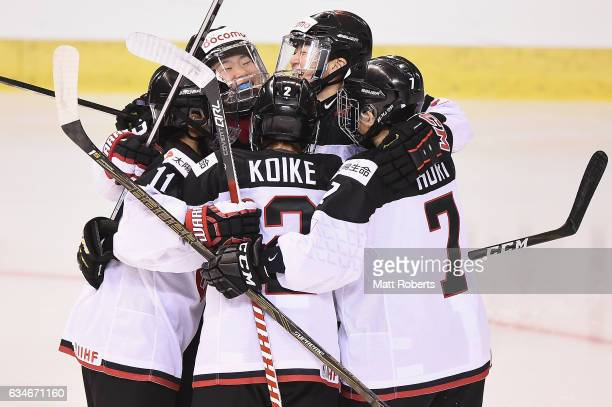 Ami Nakamura of Japan celebrates scoring a goal with team mates during the Women's Ice Hockey Olympic Qualification Final game between Japan and...