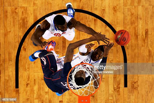Amida Brimah of the Connecticut Huskies battles for a loose ball against Patric Young and Will Yeguete of the Florida Gators during the NCAA Men's...