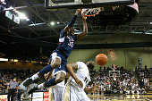 Amida Brimah of the Connecticut Huskies slam dunks the ball over Justin McBride of the UCF Knights during an NCAA basketball game at the CFE Arena on...
