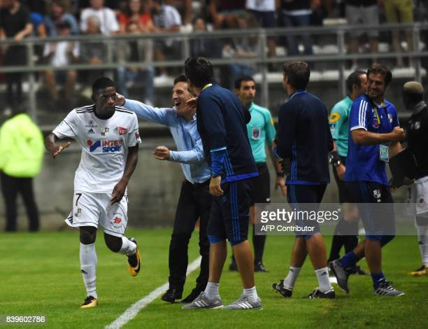 Amiens' French forward Harrison Manzala is congratuled by Amiens coach Christophe Pellissier fter scoring during the French Ligue1 football match...