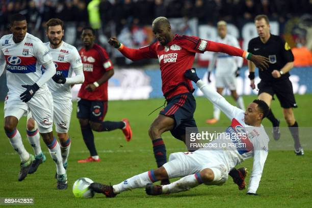 Amiens' Lacina Traore is tackled by Lyon's Dutch defender Kenny Tete during the French L1 football match between Amiens and Lyon on December 10 2017...
