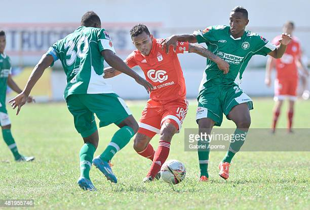 Amilcar Henriquez of America de Cali struggles for the ball with Luis Moreno and Deivy Rivas of Valledupar FC during a match between Valledupar and...