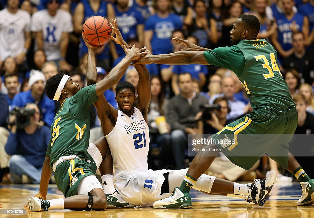 Amile Jefferson of the Duke Blue Devils tries to keep the ball away from teammates Nico Clareth and Imoh Silas of the Siena Saints during their game...