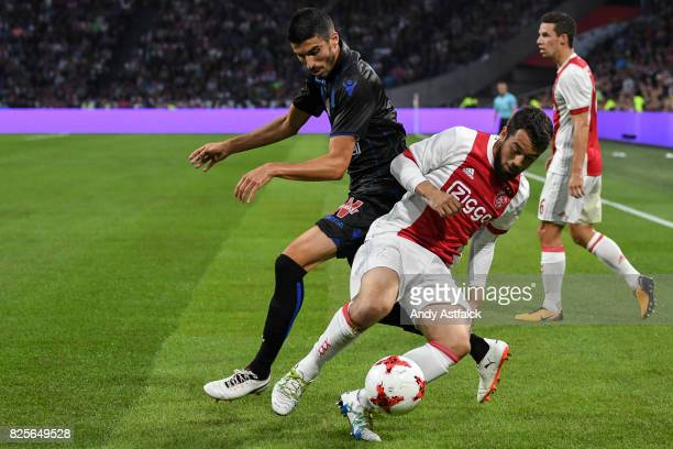 Amin Younes from AJAX is challenged by Pierre LeesMelou from OSC Nice during the UEFA Champions League Qualifying Third Round Second Leg match...