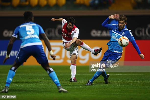 Amin Younes of Ajax is challenged by Aaron Hunt and Johan Djourou of Hamburg during a friendly match between Hamburger SV and Ajax Amsterdam at...