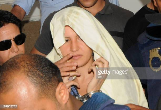Amina Sboui the Tunisian member of the Ukrainian feminist group Femen appears handcuffed with a cloth over her head before an investigating judge at...